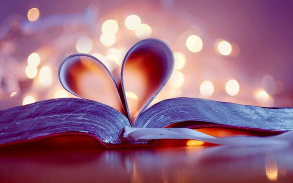 Pages of a thick book are folded into the spine to create a heart shape with blurred little lights in the background
