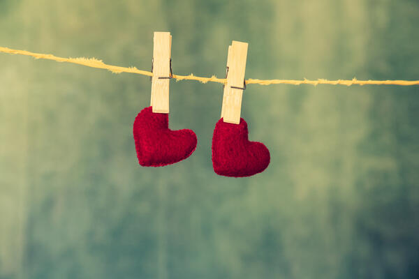 two red felt hearts clothes pinned to a line with a green and yellow abstract background