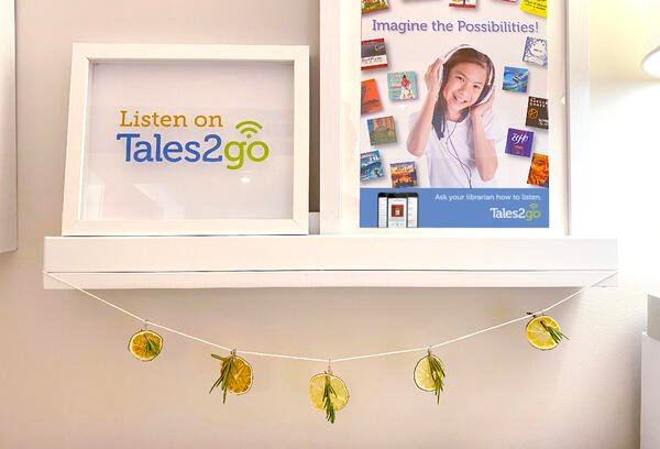 White floating shelf holding a framed Tales2go logo and a framed Tales2go poster with a dried lime and rosemary garland hanging below