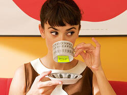 Brunette woman drinking out of a mug with her pinky up - there's a neon yellow sticky note on the bottom of the mug that says Hello!