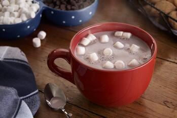 Red latte mug filled with hot chocolate with several mini marshmallows floating on top. The mug is sitting on a wooden surface with bowls of mini marshmallows, chocolate chips and cookies in the background. In the foreground are a black, grey, and white piece of fabric and a spoon containing a little bit of hot chocolate.