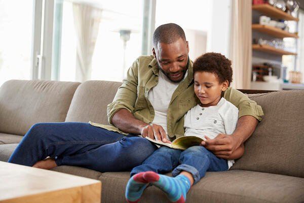 Black man and child looking at a book together on a sofa