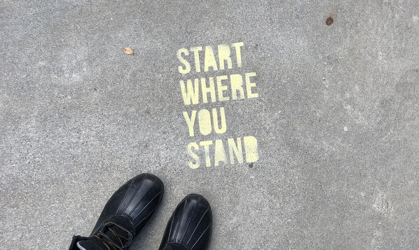 Start Where You Stand spray painted onto pavement with a person's feet in boots