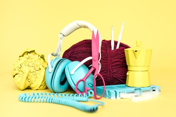 teal headphones surrounded by pink scissors, label tape, red yarn, crochet hooks and yellow teapot