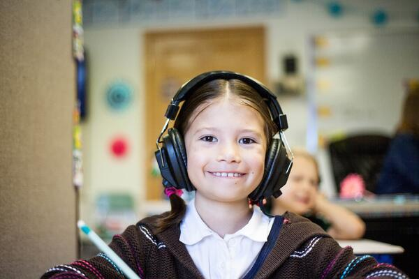 smiling second grader wearing over ear headphones