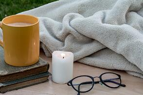 yellow mug of coffee, old books, candle, glasses, and a blanket