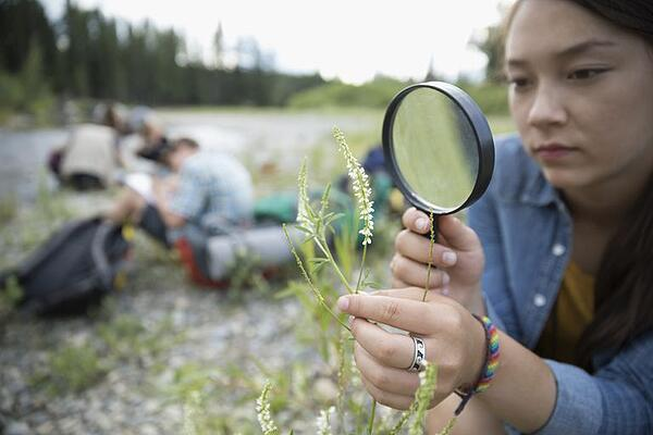 curious teenager looking at a flower through magnifying glass outside