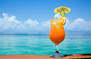 An orangey red drink in a flute with an umbrella and citrus wedge sits on a brown surface in front of a view of open blue water and a bright blue sky with fluffy white clouds
