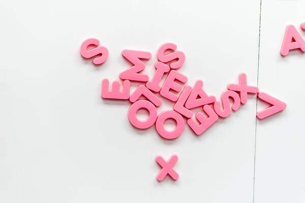 pink, sans serif capital letters jumbled on a white background